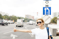 Woman standing in the street, calling taxi Stock Photo