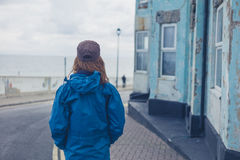Woman standing in street outside blue house Royalty Free Stock Image