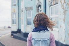 Woman standing in street outside blue house Stock Photography