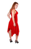 Woman standing in studio. Lovely young woman in high heels standing in the studio in a red dress, long Royalty Free Stock Photography