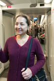 Woman standing in  subway car. Stock Image