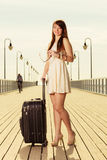 Woman standing with suitcase, pier in background Stock Photos