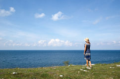 Woman standing in summer by seaside wathing the horizon Royalty Free Stock Image
