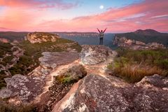 Woman standing on summit rock ledge views of sunrise valley royalty free stock photos