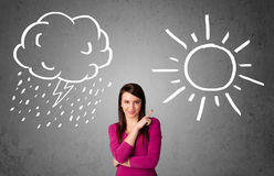 Woman standing between a sun and a rain drawing Royalty Free Stock Photography