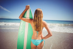 Woman standing with surfboard on beach Royalty Free Stock Photo