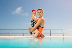 Mother and daughter in a swimming pool. Woman standing in swimming pool carrying her daughter. Mother and daughter in swimwear inside a pool stock photo
