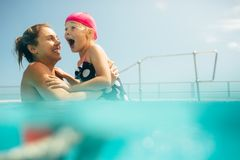 Mother and daughter having fun in the pool. Woman standing in swimming pool with her daughter looking excited. Mother and daughter in swimwear enjoying a day at stock images