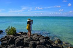 Seascape of Cap Malheureux, Mauritius. A woman standing and taking pictures in Cap Malheureux, Mauritius Royalty Free Stock Image