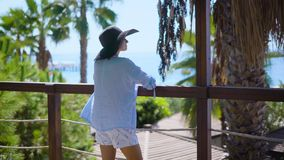 Woman standing on terrace of tropical hotel on ocean coastline. Back view of woman enjoying tropical sun on balcony of resort with palms and ocean on background stock video footage
