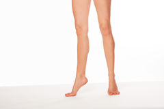 Woman standing on tip toe. Cropped view image of a pair of shapely female legs with beautiful smooth skin standing on tip toe over white with copyspace stock photography