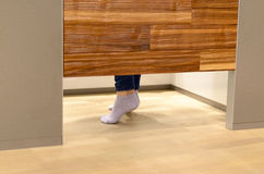 Woman standing on tip toe in a changing room. At a store as she tries on clothes, view of her feet under the wooden door royalty free stock image