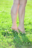 Woman standing on tiptoe on green grass Royalty Free Stock Photo