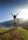 Woman standing on top of hill against bright sun with outstretch Stock Photography