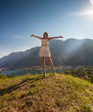 Woman standing on top of mountain and stretching out hands Royalty Free Stock Photography