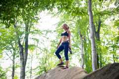 Woman standing on the top of rock after climbing boulder Stock Photography