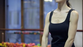Woman standing training chest, arms muscles with dumbbells indoors. Shooting of female with perfect body, actively carry out exercises. Beautiful, charming stock footage