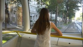 Woman standing in the tram and looking outside. Beautiful young woman standing in the tram and looking outside to the passing streets of Vienna, Austria. Public stock video