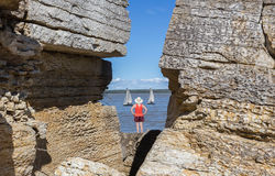 Woman standing between two rock cliffs watching sailboats float by. Stock Photography