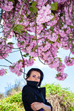 Woman standing under blooming tree and blue sky Stock Photography