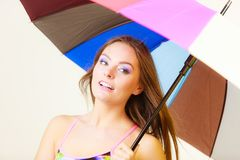 Woman standing under colorful rainbow umbrella Stock Images