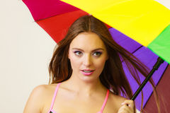 Woman standing under colorful rainbow umbrella Stock Photography