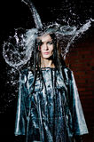Woman Standing Under Deluge. Woman standing under a deluge of water pouring from above her head, upper body pose outside with dark brick wall Stock Photos