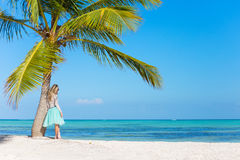 Woman standing under palm tree on tropical beach Royalty Free Stock Photography