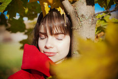 Woman Standing Under The Tree. Portrait of a young woman in autumn, she is standing under the tree with her eyes closed royalty free stock photos