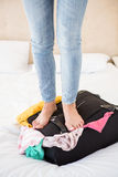Woman standing up on her suitcase Royalty Free Stock Images