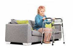 Woman standing up from a sofa with walker Stock Photos