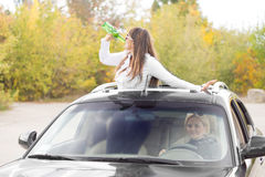 Woman standing up through a sunroof drinking Stock Photography