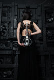 A woman is standing with violin back to the photographer Stock Photo