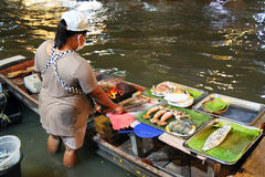 Woman standing in water is cooking seafood for tourists on floating market. Bangkok, Thailand.