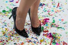 Woman standing wearing black heels standing on the confetties Stock Image