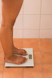 Woman Standing on a Weighing Scale at Home Royalty Free Stock Photography