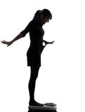 Woman standing on weight scale  happy silhouette Stock Photography