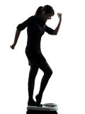 Woman standing on weight scale  happy silhouette Stock Photo