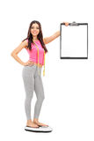 Woman standing on weight scale and holding a clipboard. Woman standing on a weight scale and holding a clipboard isolated on white background stock photo