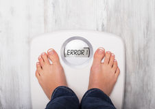 Woman standing on weight scale showing error message. Woman standing on weight scale that is showing error message stock photography