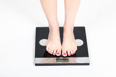 Woman standing on weight scales. Woman standing on digital weight scales, on clear background Stock Images