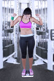 Woman standing on weight scales at gym. Successful indian woman wearing sportswear and standing on weight scales at gym Royalty Free Stock Photography