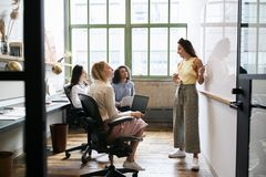 Woman standing at whiteboard in a meeting with female team stock image