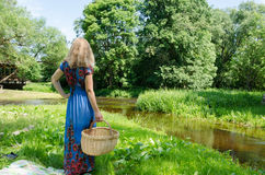 Woman standing with wicker basket in meadow Royalty Free Stock Images