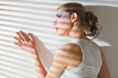 Woman standing by the window with blinds Royalty Free Stock Image