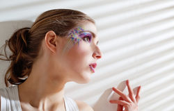 Woman standing by the window with blinds Stock Photography