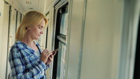 A woman is standing by the window in the corridor of a passenger railway car. Uses a mobile phone stock video footage