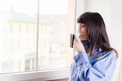 Woman standing by the window drinking coffee Royalty Free Stock Image