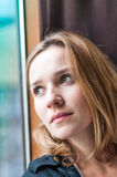 Woman standing by a window looking outside Stock Photography