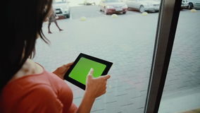 Woman standing by the window and using a tablet . green screen stock video footage